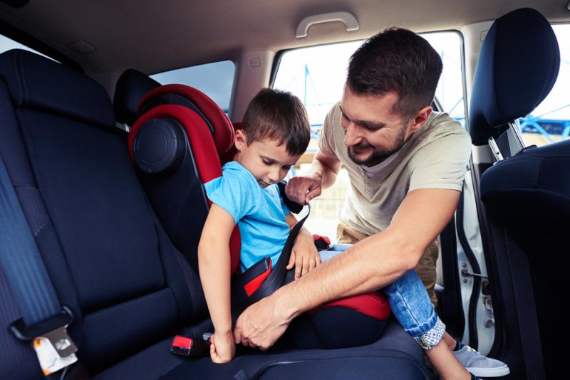 a father helping his kid to set in a car seat