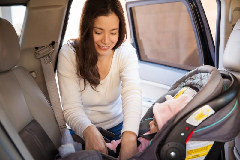 a mom helping putting her kid in a car seat
