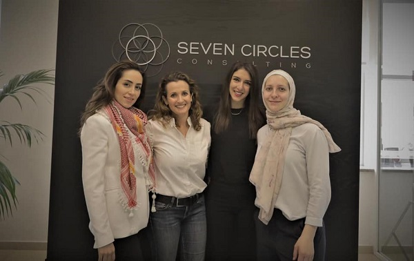 4 women standing in front of a wall that has seven circle's logo in it