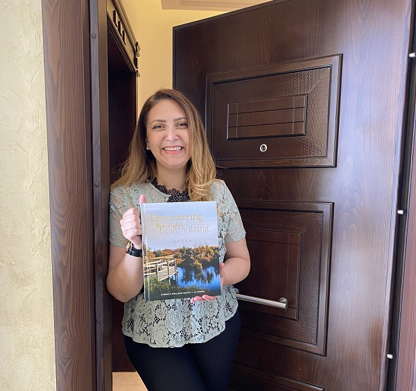 woman smiling and holding the Empowering Women through Healthy Living book