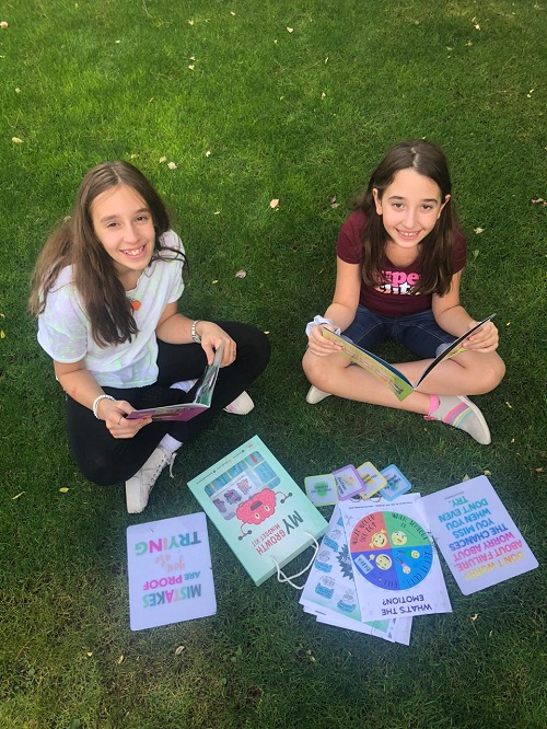 two girls reading books from the growth mindset kit