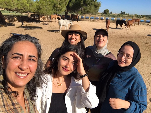 A group of women enjoying their time with horses behind them