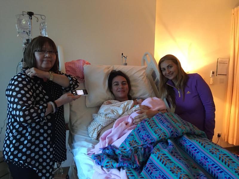 صورة لأم و طفلتها على سرير المشفى برفقة الدولا الخاصة بها