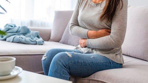 امرأة تتألم وتضع يديها على بطنها
