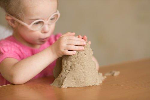 طفلة من ذوي الاحتياجات تلعب بالصلصال والرمل