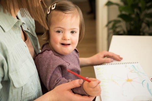 طفلة من ذوي الاحتياجات ترسم وتلون