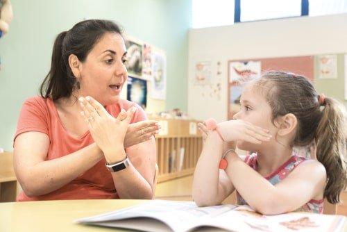 طفلة من ذوي الاحتياجات تتعلم القراءة