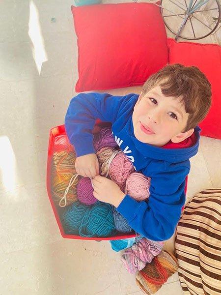 a little boy holding a box full of yarn